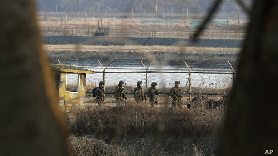 South Korean army soldiers patrol along a barbed-wire fence near the border village of Panmunjom in Paju, South Korea, March 27, 2013.