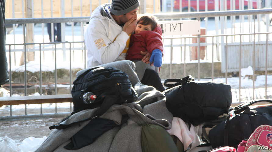A man and child try to keep warm as they wait at the migrant and refugee registration center in Presevo, Serbia, Jan. 19, 2016. (P. Walter Wellman/VOA)