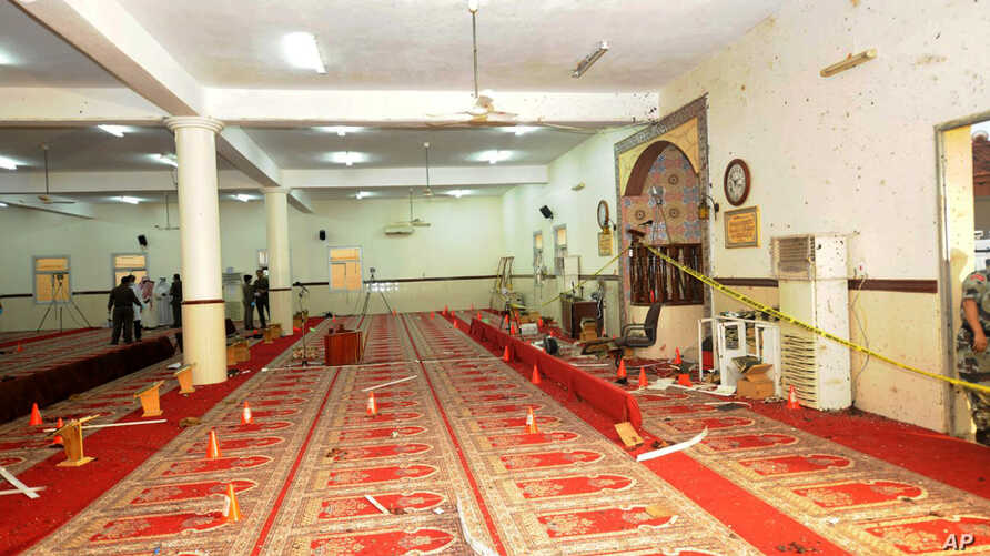 In this photo released by the Saudi Press Agency SPA, Saudi officials and investigators, background, check a mosque inside a police compound after a suicide bombing attack, in the city of Abha, the provincial capital of Asir, Saudi Arabia, Aug. 6, 20...