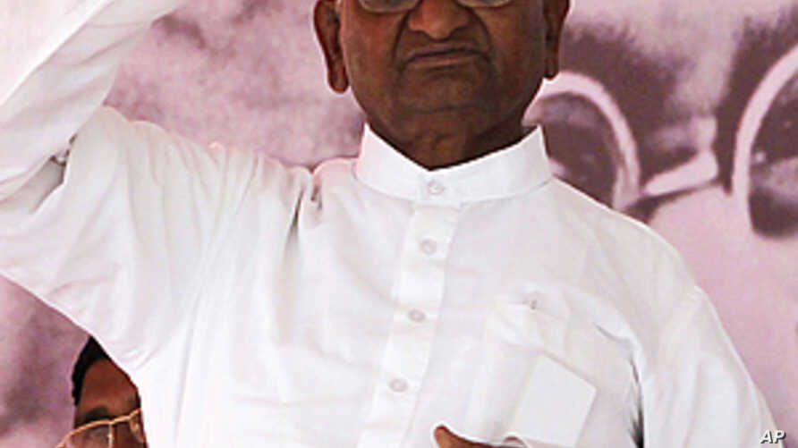Indian anti-corruption activist Anna Hazare waves to supporters next to a portrait of Mahatma Gandhi on the first day of his hunger strike in Mumbai, India, December 27, 2011.
