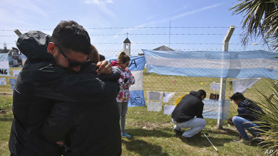 Relatives and friends of Alejandro Tagliaprieta, a crew member on the missing ARA San Juan submarine, embrace at the naval base where people hang flags and messages on the fence in Mar de Plata, Argentina, Nov. 24, 2017.