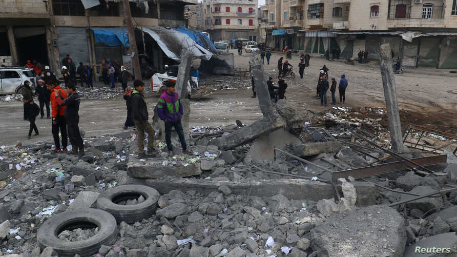 People inspect a site hit by airstrikes at a parking garage in the rebel-held city of Idlib, Syria, Jan. 18, 2017.