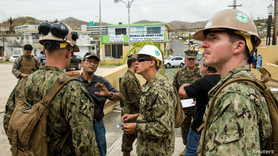 U.S. Marines and Navy corpsmen attached to the 26th Marine Expeditionary Unit and sailors assigned to Amphibious Construction Battalion 2 speak with local civilian employees during an assessment of Hospital Oriente's needs as part of Hurricane Maria