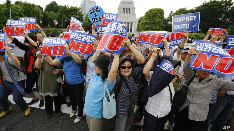 FILE - Protesters against the construction of the new U.S. base in Okinawa hold placards in front of the National Diet building during a rally in Tokyo, May 24, 2015. A crowd estimated at 70,000 gathered Saturday in a park in the state capital of Nah