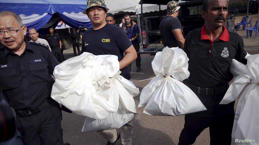 Forensic policemen carry body bags with human remains found at the site of human trafficking camps in the jungle close the Thailand border after they brought them to a police camp near Wang Kelian in northern Malaysia, May 25, 2015.