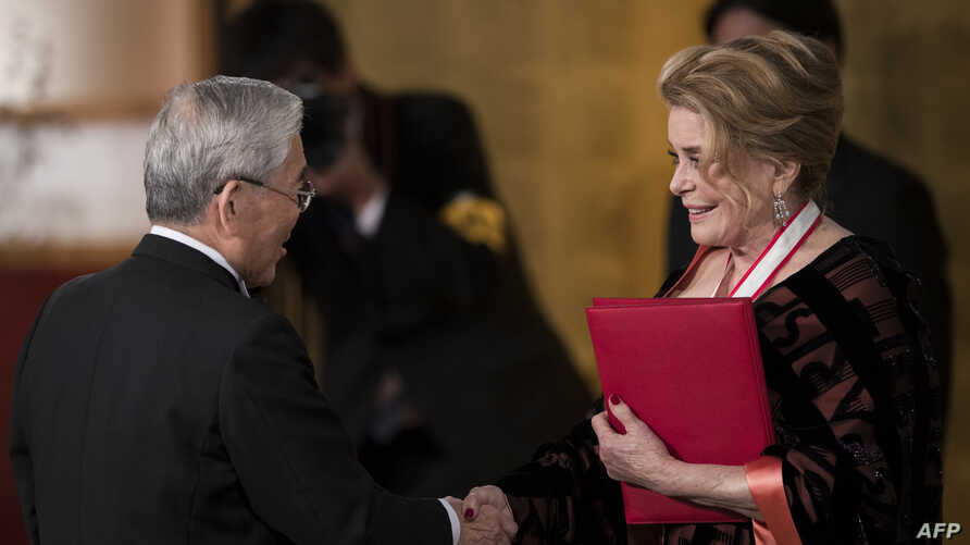 French actress Catherine Deneuve (R), a winner of the 30th Praemium Imperiale award receives her certification during the award ceremony in Tokyo, Oct. 23, 2018.