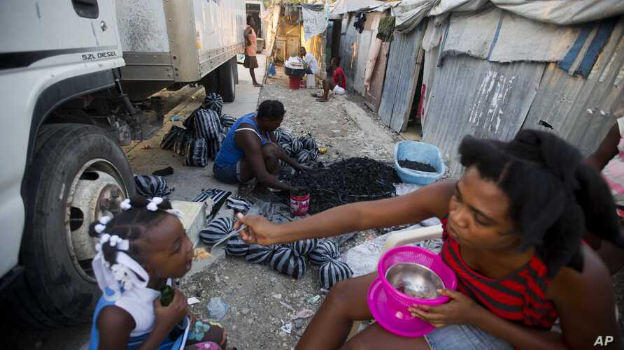 FILE - Adrienne St. Fume bags charcoal outside her shelter in the Delmas tent camp in Port-au-Prince, Haiti, Dec. 5, 2016. The camp was set up for people displaced by the 2010 earthquake. The U.S. government is reviewing Temporary Protected Status fo