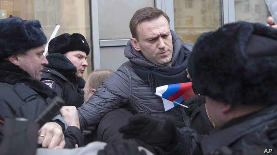FILE - Russian opposition leader Alexei Navalny (C) is detained by police officers in Moscow, Jan. 28, 2018.