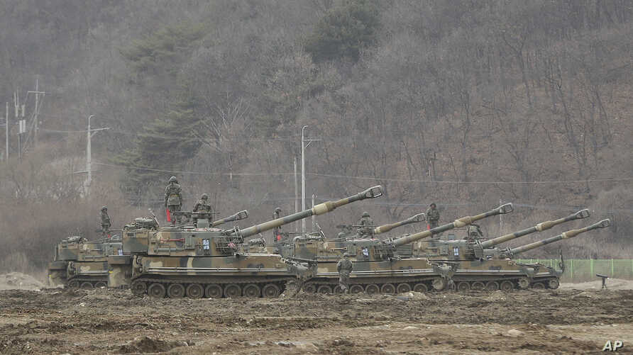 South Korean army soldiers stand on their K-55 self-propelled howitzers during an annual exercise in Paju, near the border with North Korea, Monday, March 7, 2016.