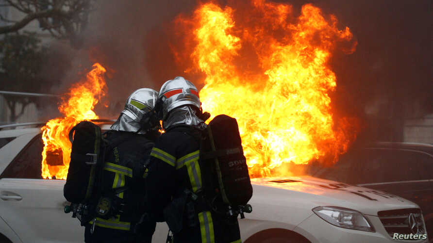 Firefighters try to extinguish flames from a burning car during a demonstration of the yellow vest movement in Nantes, France, Jan. 12, 2019.