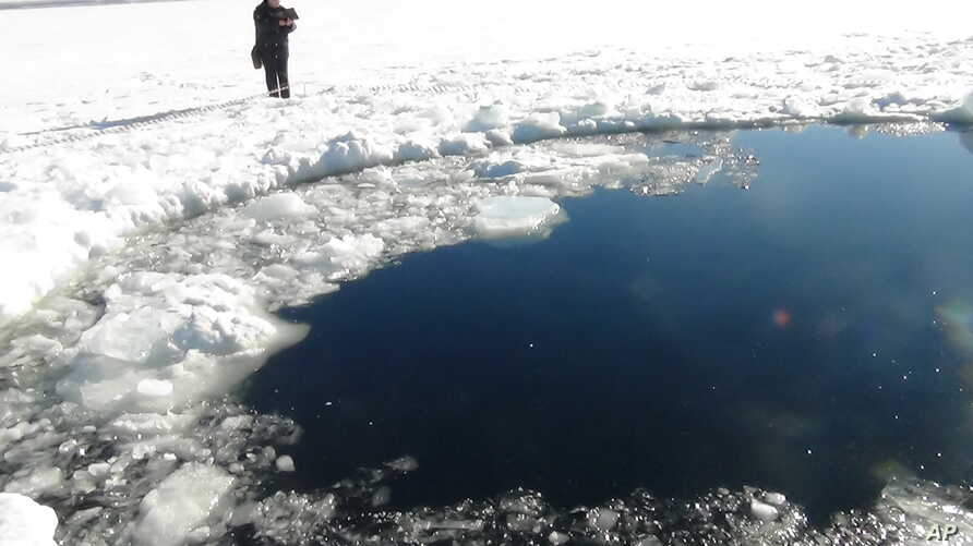A circular hole in the ice of Chebarkul Lake where a meteor reportedly struck the lake near Chelyabinsk, about 1500 kilometers (930 miles) east of Moscow,  February 15, 2013