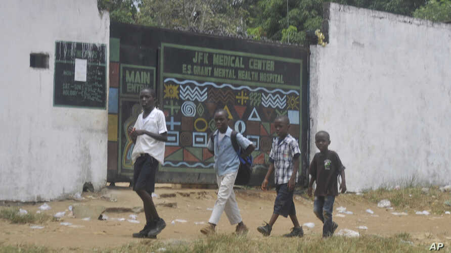 Children walk past JFK Medical centre in Monrovia, Liberia. Ebola centers.  The trauma of the world's deadliest Ebola outbreak, which killed more than 11,300, has left many survivors fighting a mental health battle to focus on the present, after witn