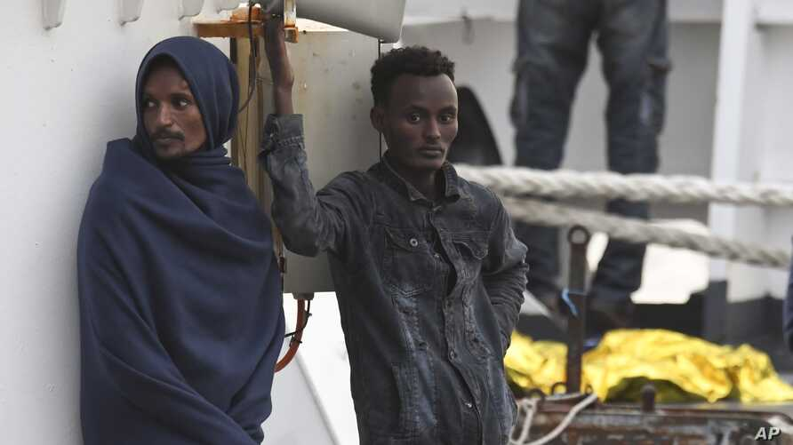 Migrants stand aboard the Italian Coast Guard ship Diciotti, moored at the Catania harbor, Aug. 21, 2018.