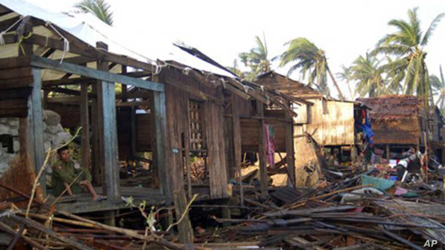In this photo taken on Sunday, Oct. 24, 2010, a soldier sits at a house destroyed by Cyclone Giri in Myaypon in western Rakhine State, in Burma.