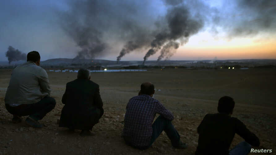 Kurdish refugees watch from a hilltop as thick smoke rises from the Syrian town of Kobani during heavy fighting between Islamic State and Kurdish Peshmerga forces, seen from near the Mursitpinar border crossing on the Turkish-Syrian border, Oct. 26, ...
