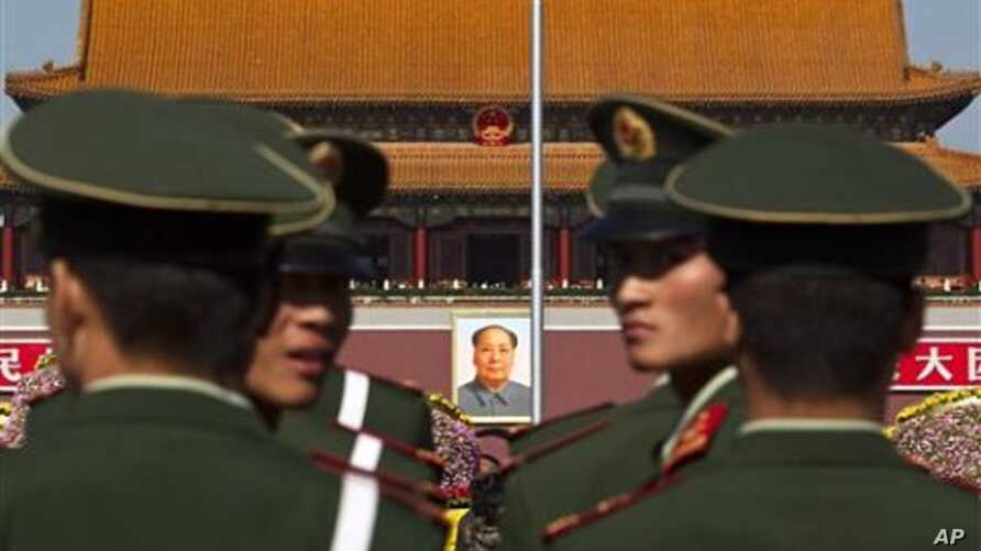 Paramilitary policemen look back while patrolling on the Tiananmen Square in front of the late communist leader Mao Zedong's portrait in Beijing, China, 15 Oct. 2010