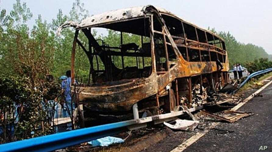 Chinese police investigate the burnt wreckage of a double-decker bus after the bus was carrying hazardous goods and caught fire on a highway in Xinyang, in north China's Henan province on July 22, 2011