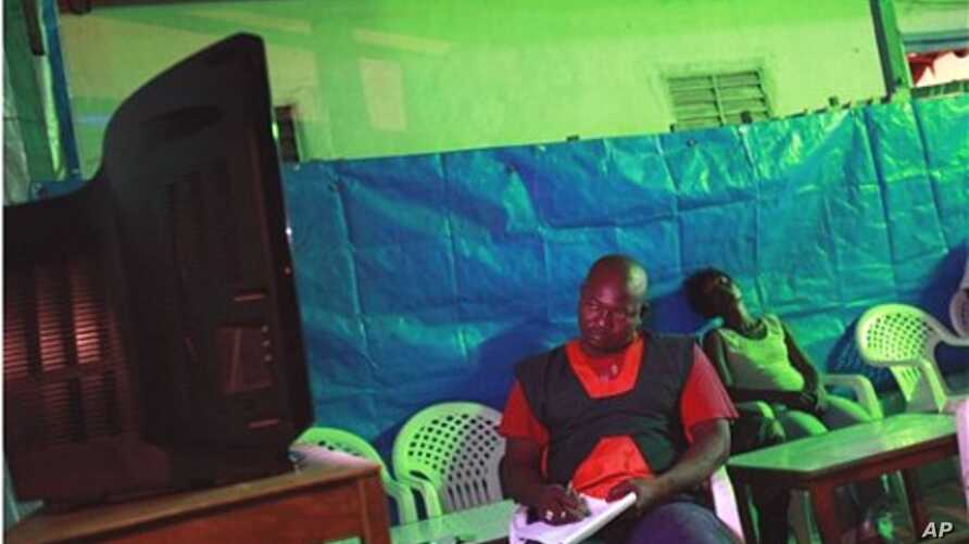 Owner of an open-air bar and restaurant Zakarya Gueme takes notes as partial election results are announced on state television, in central Bouake, the former rebel capital of northern Ivory Coast, 02 Nov 2010