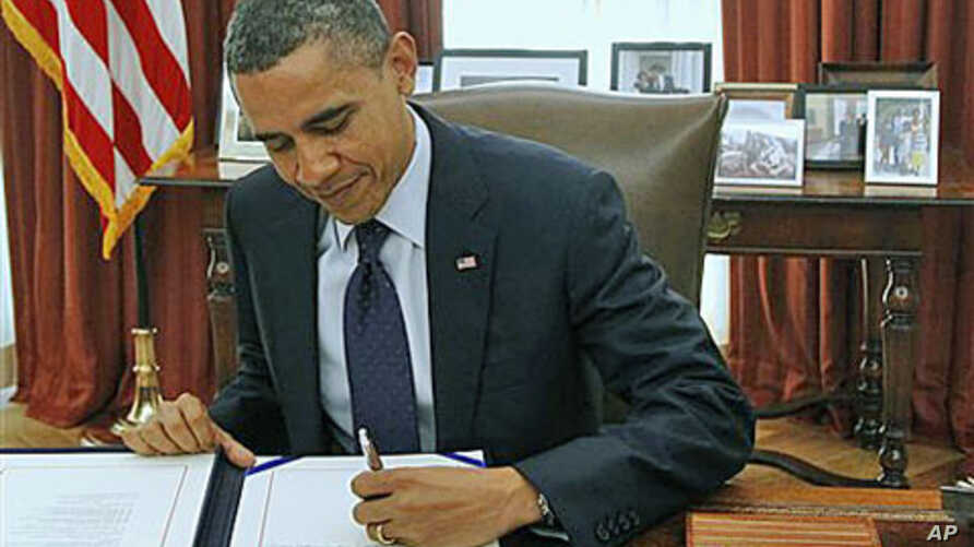 President Barack Obama signs the payroll tax cut extension in the White House Oval Office, in Washington, December 23, 2011.