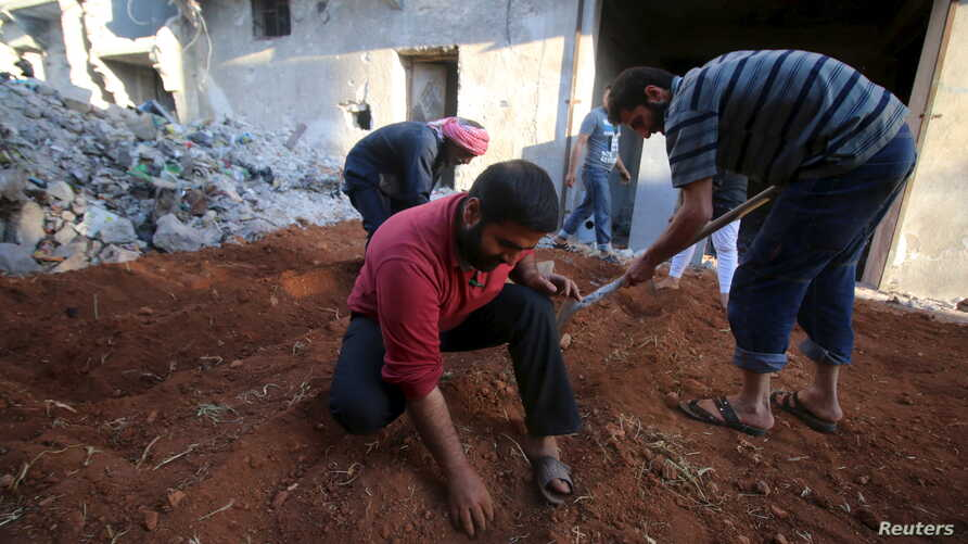 FILE - Residents grow their own vegetables near the rubble of damaged buildings in the rebel held area of al-Jazmati neighborhood of Aleppo, Syria  April 22, 2016.