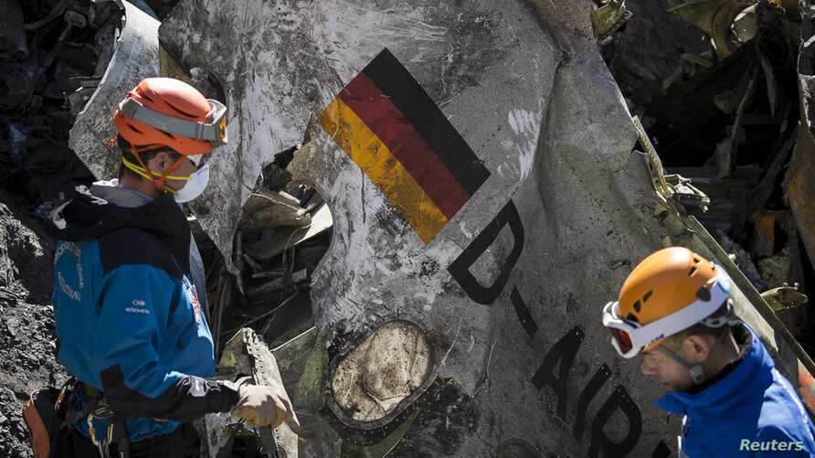 French gendarmes, seen in this picture made available to the press by the French Interior Ministry April 1, 2015, work near debris from wreckage showing a German flag at the crash site of an Airbus A320, near Seyne-les-Alpes.