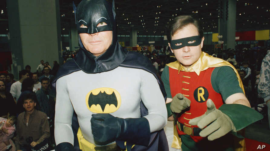 """FILE - Actors Adam West, left, and Burt Ward, dressed as their characters Batman and Robin, pose for a photo at the """"World of Wheels"""" custom car show in Chicago, Jan. 27, 1989."""