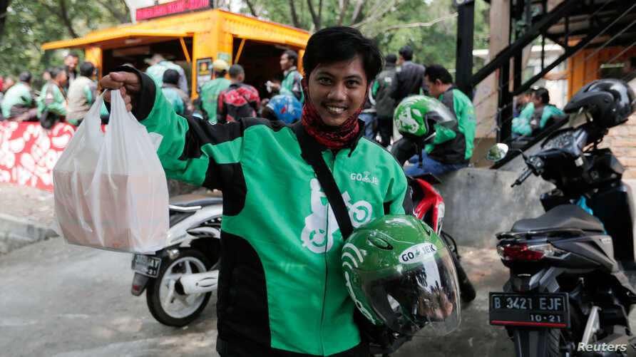 A Go-Jek driver shows boxes with food for his customer in front of a food stall in Jakarta, Indonesia, July 13, 2017.