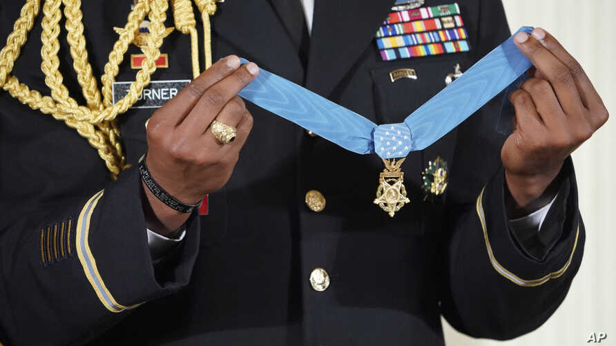 FILE - A military aide holds up the nation's highest military honor, the Medal of Honor, during a ceremony in the East Room of the White House in Washington, Oct. 23, 2017.