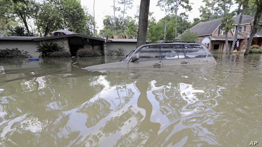 FILE - A car is submerged in floodwaters in the aftermath of Hurricane Harvey near the Addicks and Barker Reservoirs in Houston, Sept. 4, 2017.