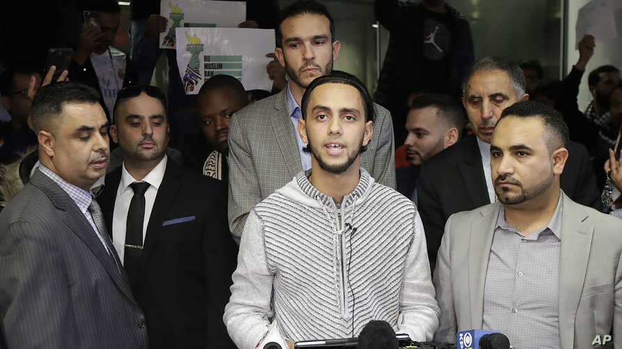 Ali Hassan, center, speaks at a news conference after his wife, Shaima Swileh, hidden, arrived at San Francisco International Airport in San Francisco, Dec. 19, 2018. Swileh is the Yemeni mother who won her fight for a waiver from the Trump administr...