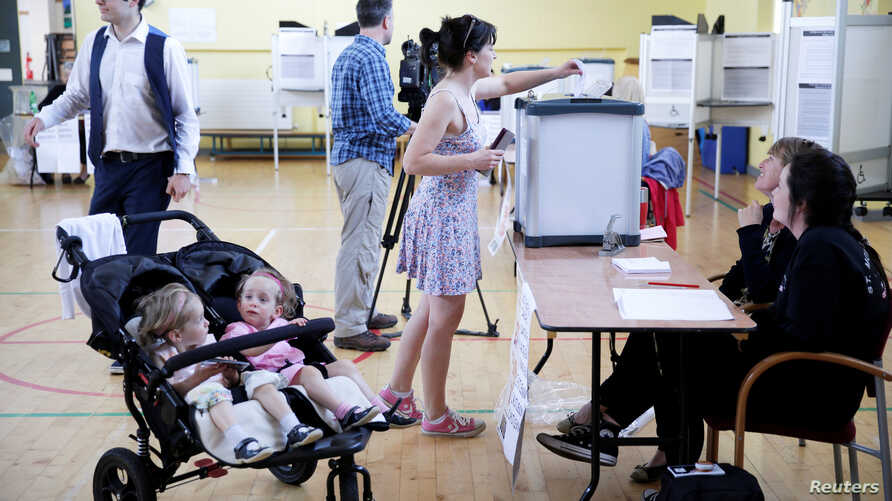 A woman votes while her children wait in their stroller as Ireland holds a referendum on liberalizing its law on abortion, in Dublin, Ireland, May 25, 2018.