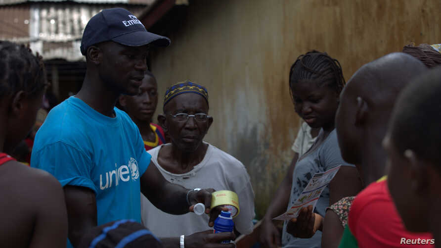 FILE - A UNICEF worker shares information on Ebola and how to help prevent its spread in Conakry, Guinea in this UNICEF handout photo.