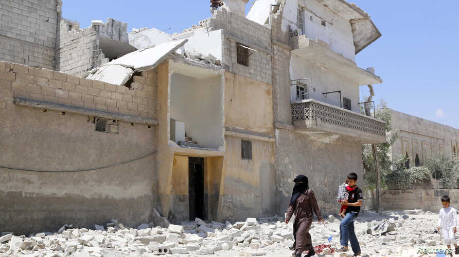 FILE - Civilians make their way on a street littered with the rubble of buildings damaged by air strikes in Aleppo, May 14, 2014.