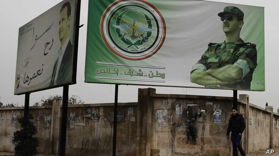 """FILE - A man walks by posters of Syrian President Bashar al-Assad that in Arabic read """"Homeland, honor, fidelity. Together we will build it,"""" in Aleppo, Syria, Dec. 5, 2016."""