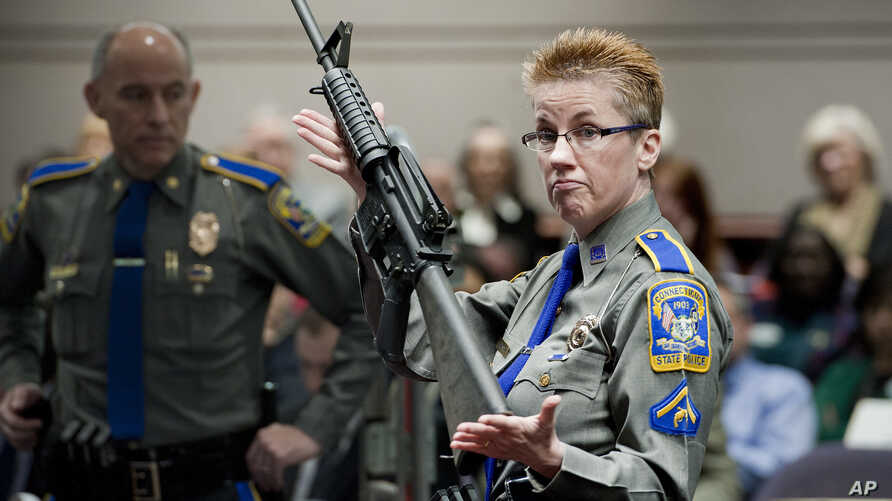 FILE -Ffirearms training unit Detective Barbara J. Mattson, of the Connecticut State Police, holds a Bushmaster AR-15 rifle, the same make and model used by Adam Lanza in the 2012 Sandy Hook School shooting, in this Jan. 28, 2013 photo.
