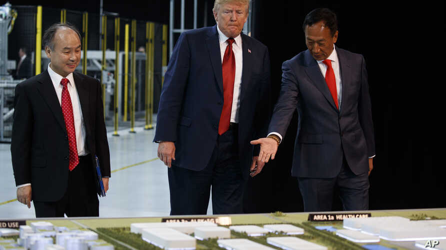 President Donald Trump takes a tour of Foxconn with Foxconn chairman Terry Gou, right, and CEO of SoftBank, Masayoshi Son, June 28, 2018, in Mt. Pleasant, Wisconsin.