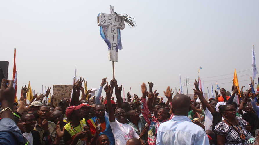 FILE - Supporters of Congo opposition leader Etienne Tshisekedi, rear, hold up a cross that symbolizes no third term for DRC President Joseph Kabila, during a political rally in Kinshasa, DRC, July 31, 2016.