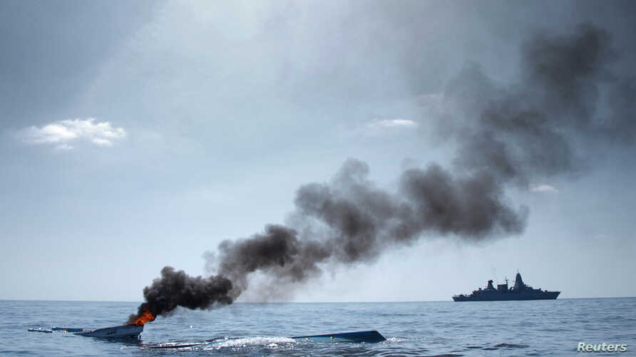 As part of the EU Naval Force Somalia, the German Frigate 'Hamburg' patrols after destroying two fishing boats (L) which were discovered floating keel side up in open waters off the coast of Somalia, August 15, 2011.