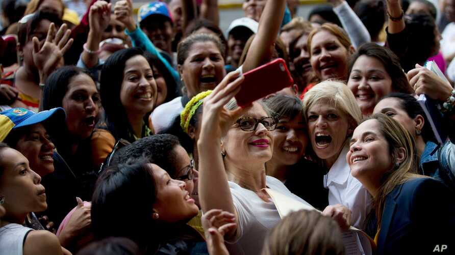 Opposition Congresswoman Adriana Delia, center, poses for a photo with supporters during a protest asking for a referendum against Venezuela's President Nicolas Maduro, outside the National Electoral Council, in Caracas, Venezuela, July 19, 2016.