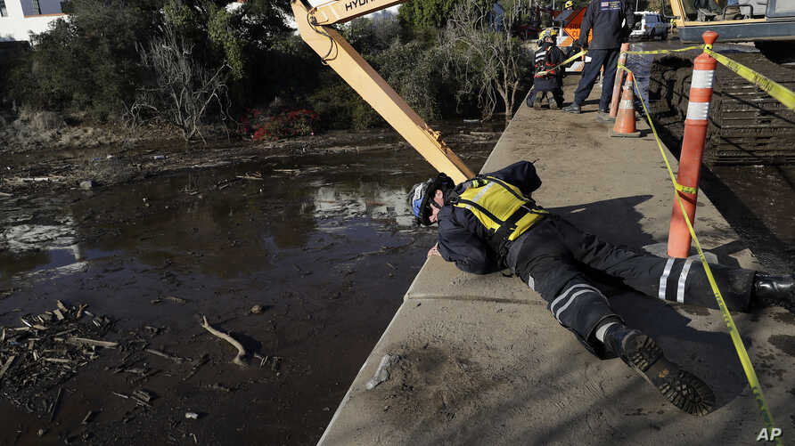 An emergency worker looks down from an overpass toward a flooded area of Highway 101 in Montecito, Calif., Jan. 11, 2018.