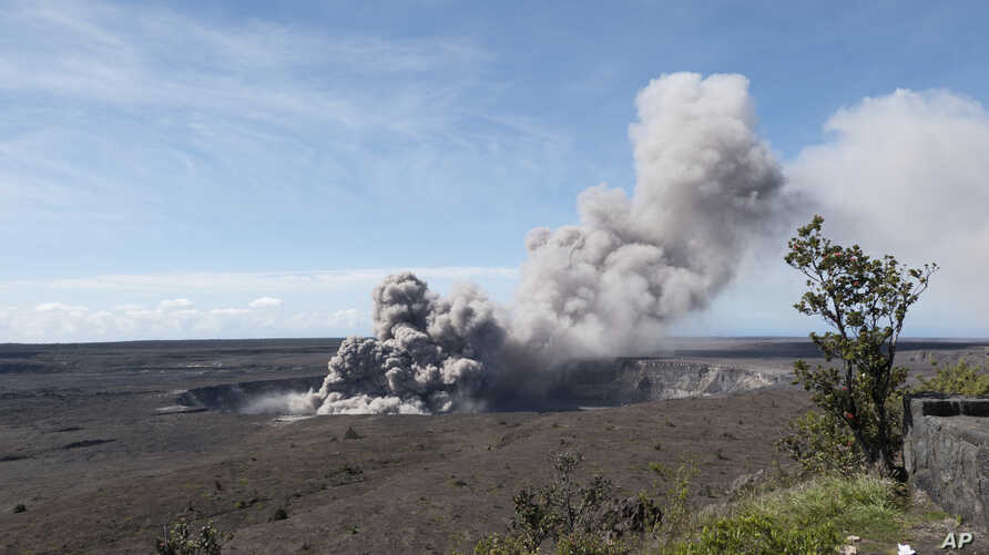 In this May 11, 2018, photo released by the U.S. Geological Survey, a weak ash plume rises from the Overlook Vent in Halema'uma'u crater of the Kilauea volcano on the Big Island of Hawaii. Geologists warn that the volcano could shoot out large boulde