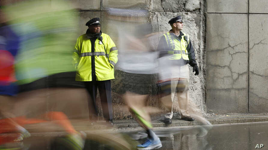 FILE - Police officers stand watch as Boston Marathon participants race along the course in Boston, April 20, 2015.