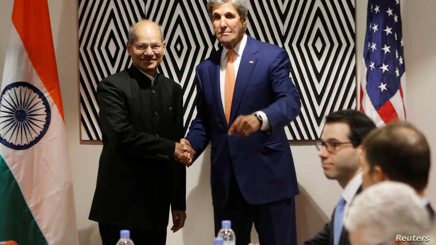 U.S. Secretary of State John Kerry shakes hands with Anil Madhav Dave, India's minister of environment, forest and climate change, before holding a bilateral meeting to promote U.S. climate and environmental goals at the Meeting of the Parties to th