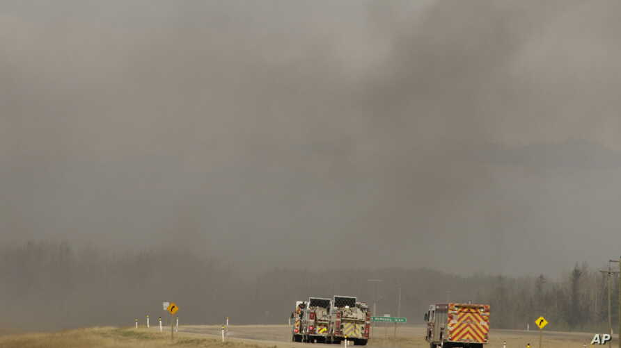 """Fire trucks drive toward smoke from a wildfire near Fort McMurray, Alberta, Canada, May 8, 2016.  Officials said Sunday they were hoping to get a """"death grip"""" on the blaze amid cooler temperatures."""