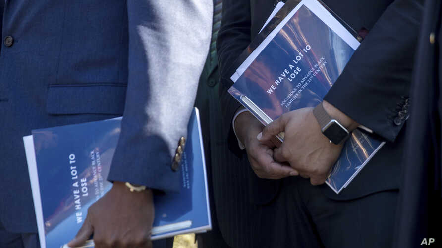 """Members of the Congressional Black Caucus hold pamphlets that read """"We Have a Lot to Lose"""" as they speak to members of the media after meeting with President Donald Trump in the Cabinet Room of the White House, March 22, 2017, in Washington. Caucus m"""