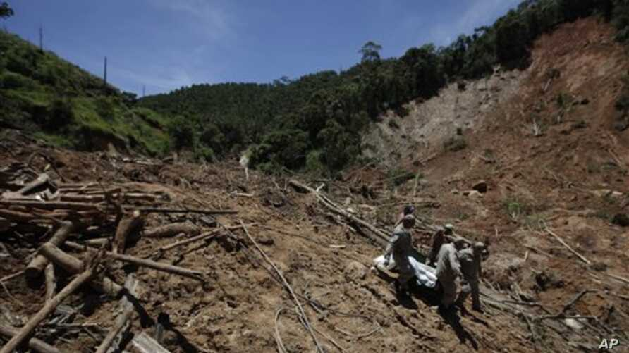 Firefighters, a National Force soldier and residents carry the body of a landslide victim from a home where the bodies of eight family members were found in Nova Friburgo, Rio de Janeiro state, Brazil, 20 Jan 2011