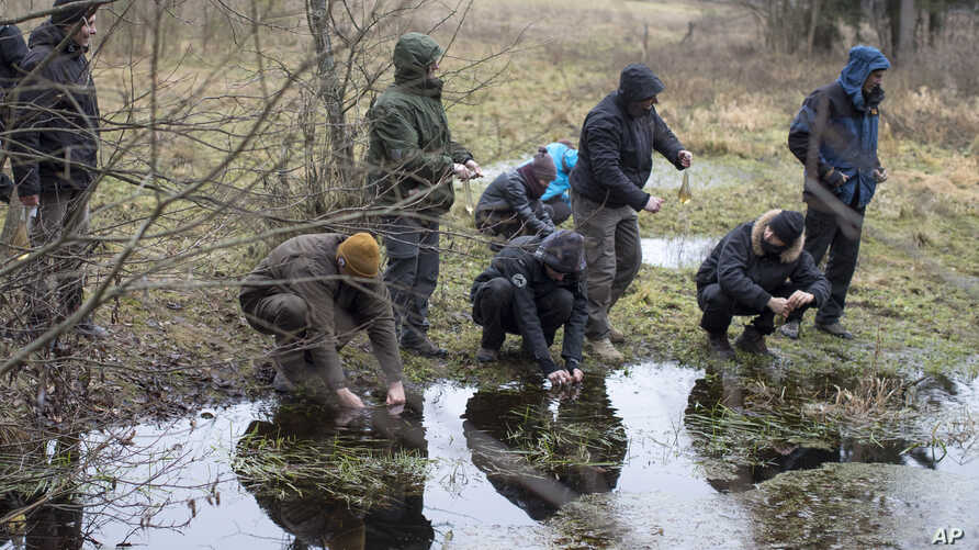 Lithuanian civilians use condoms to gather water from a creek during a survival course teaching them skills that some fear could be needed given Russia's resurgence, just outside of the capital Vilnius, Lithuania, Nov. 26, 2016.