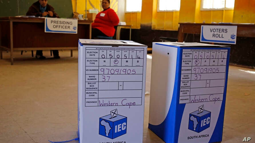 Ballot boxes await voters as Election officials (background) await their arrival after they opened early for disabled people to vote in Nyanga township before Wednesdays official elections on the outskirts of the city of  Cape Town, South Africa, May