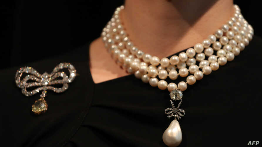 In this file photo taken on Oct. 19, 2018, a model wears the 'Queen-Marie Antoinette's Pearl.' and a diamond brooch belonging to Queen Marie-Antoinette.