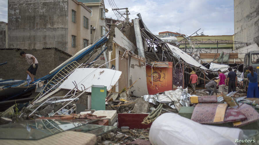 People clear debris after Typhoon Rammasun hit Zhanjiang, Guangdong province, China, July 20, 2014.